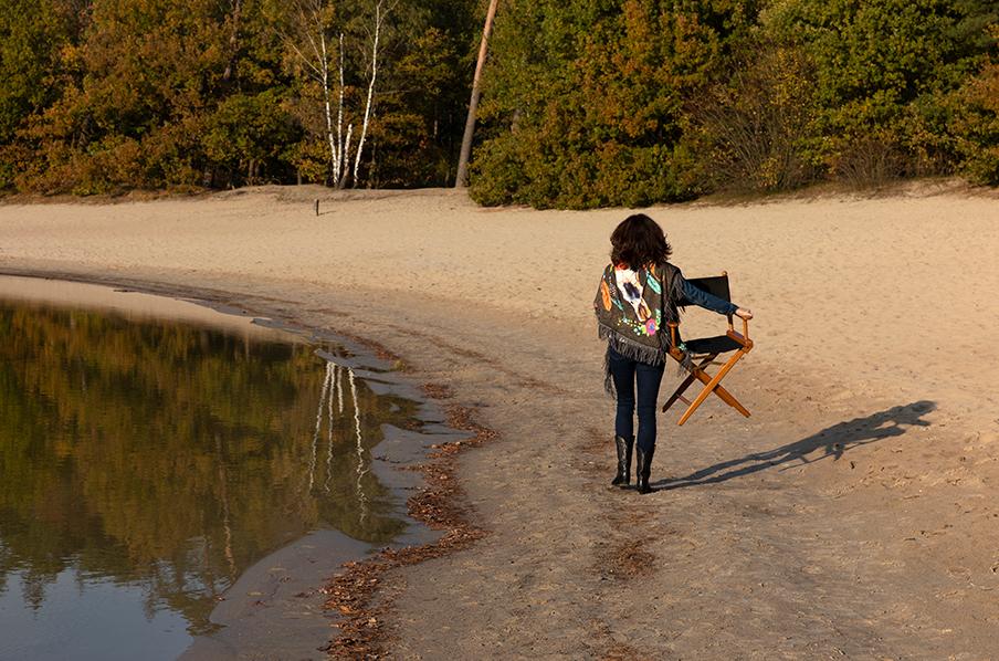 Caroline van Dijk loopt met een stoel langs het strand