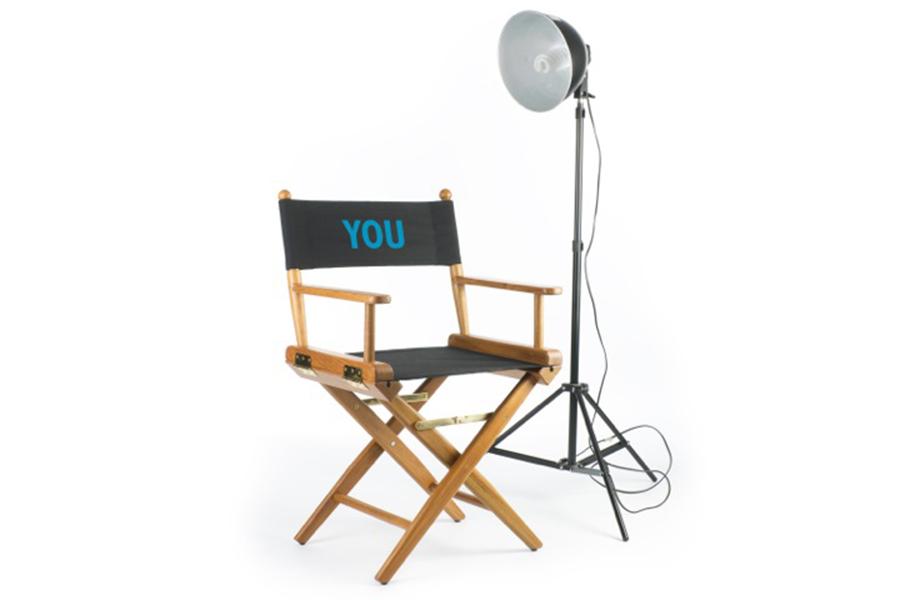 Regisseursstoel in witte ruimte met lamp op statief