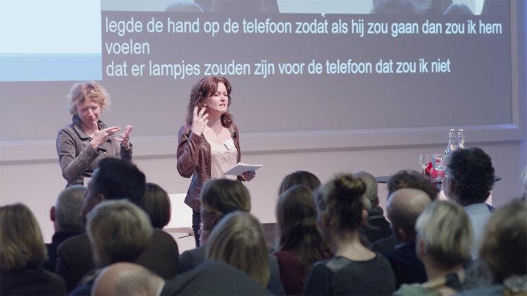 Coach Caroline van Dijk voor een zaal met publiek